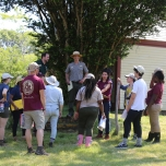 Debriefing the Inventory Team: Bill Burke (center, with brimmed hat) explains the history of the site to the group in the shade of a large tree-of-heaven. Behind him is the north façade of the main house.