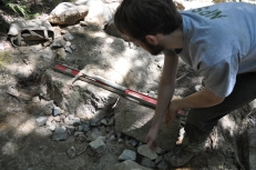 A member of the trails crew works to install a new stone check.